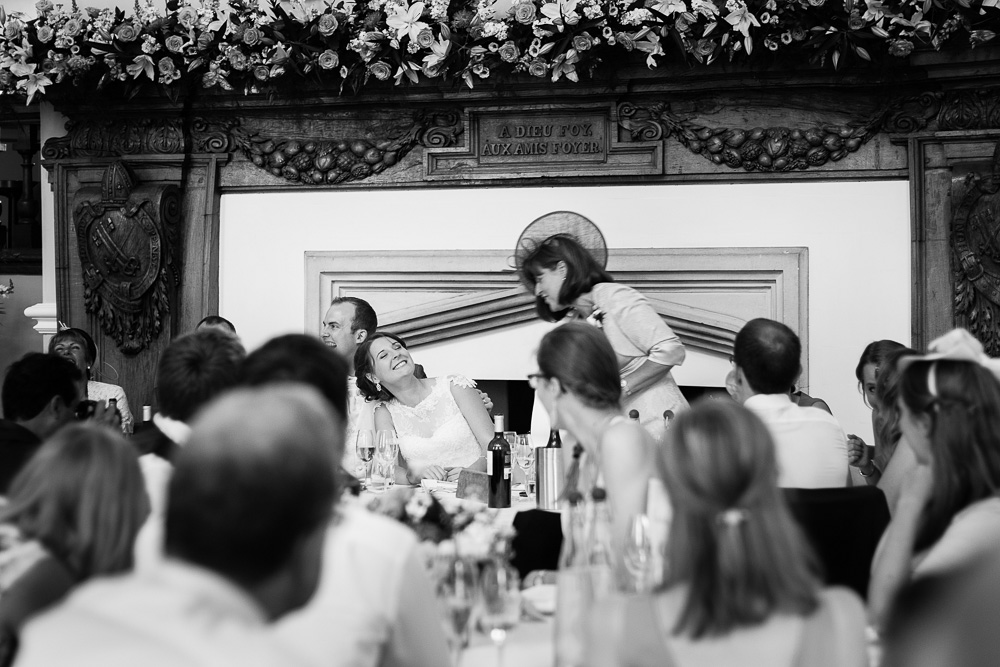 black and white lauhing bride during speeches