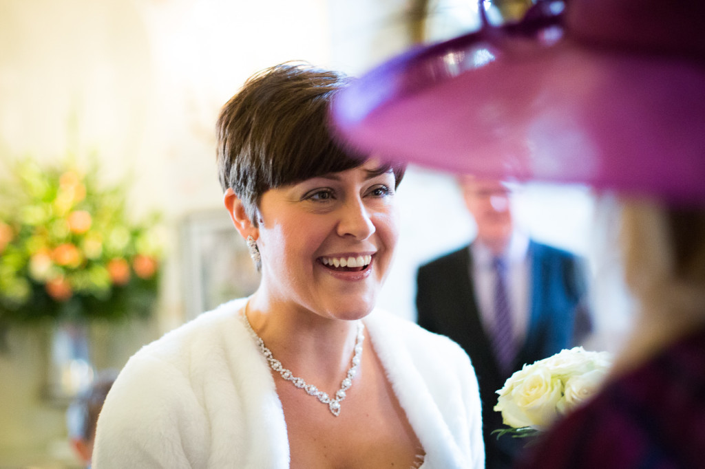 Bride in white smiling at guest