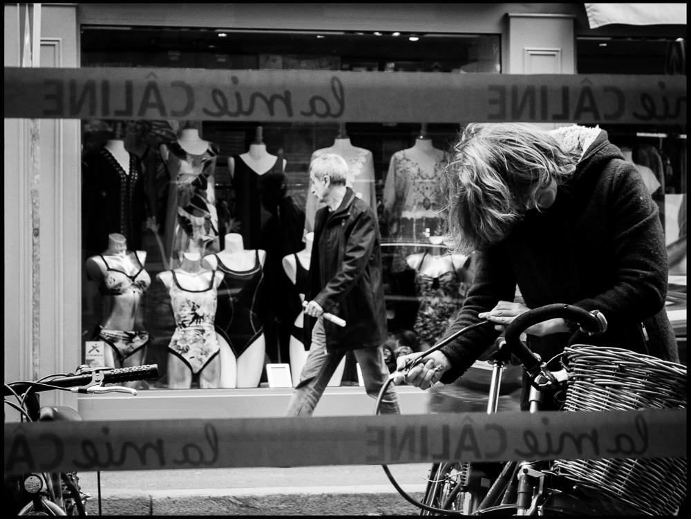 Man walking past shop black and white