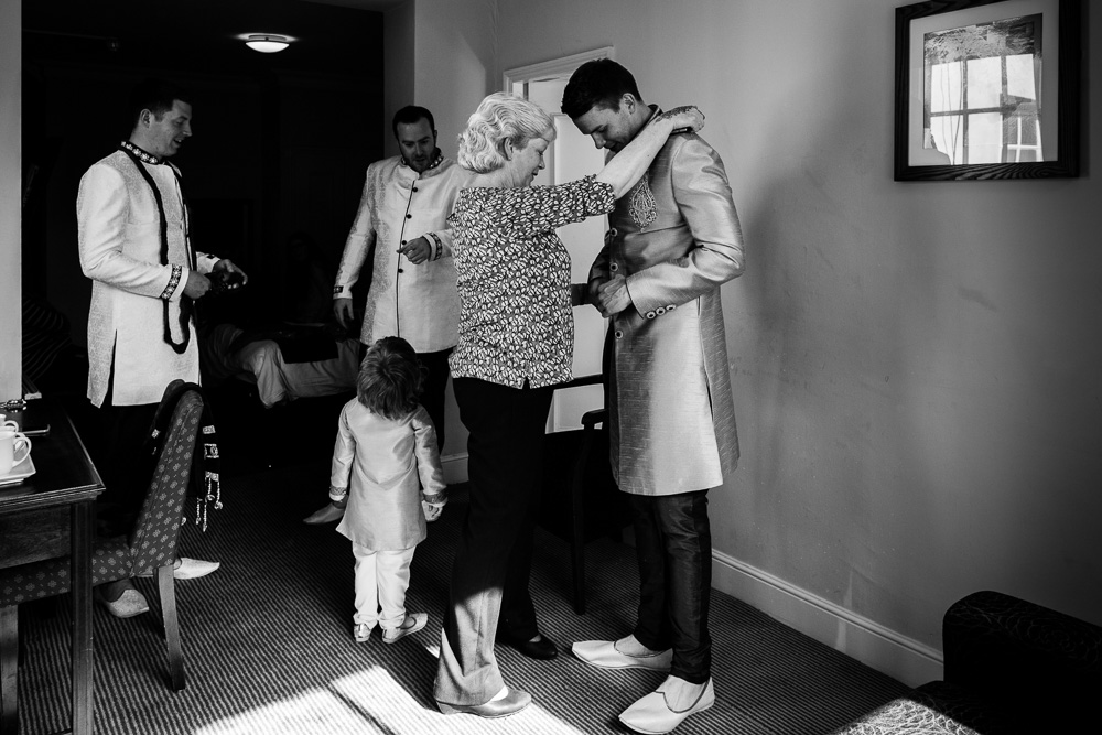black and white picture of groom and family getting ready in hotel room