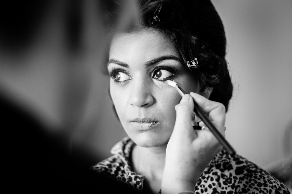 black and white picture of bride having her makeup done
