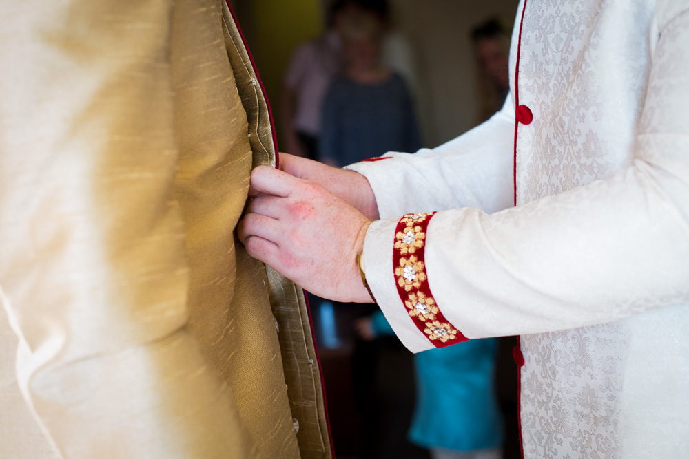 groom buttoning up his father