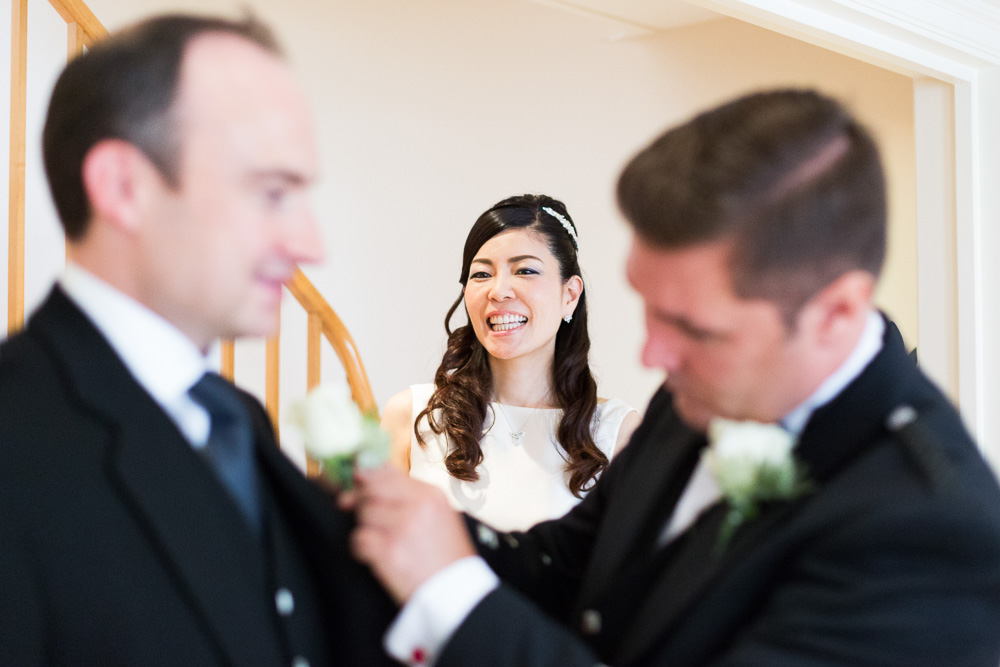 bride laughing with the groom and best man