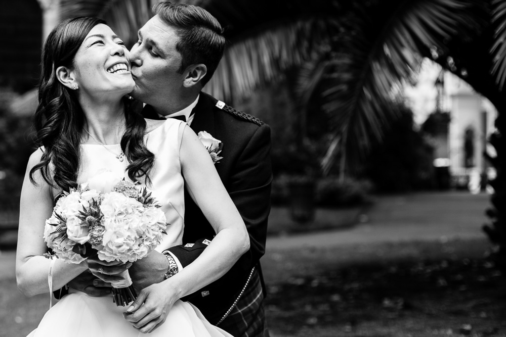 black and white image of cuddling bride and groom
