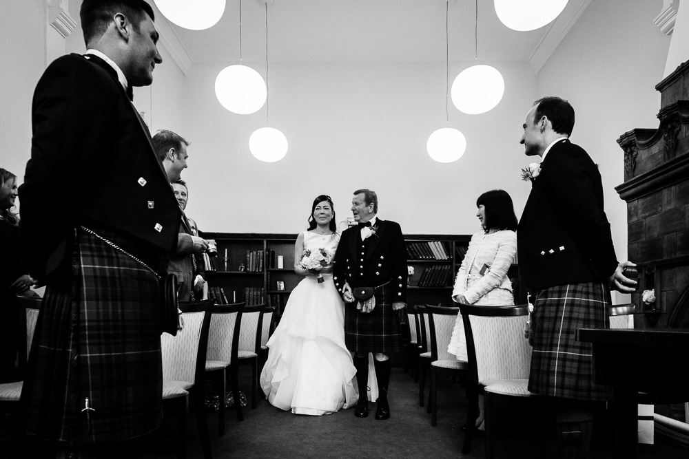 emotional black and white shot of bride walking down the aisle