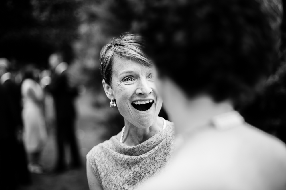 black and white shot of smiling wedding guest