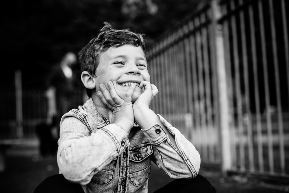 black and white shot of boy holding his chin with his hands laughing