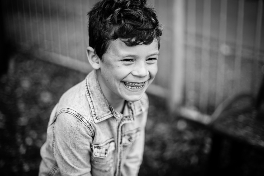 black and white portrait of little boy laughing