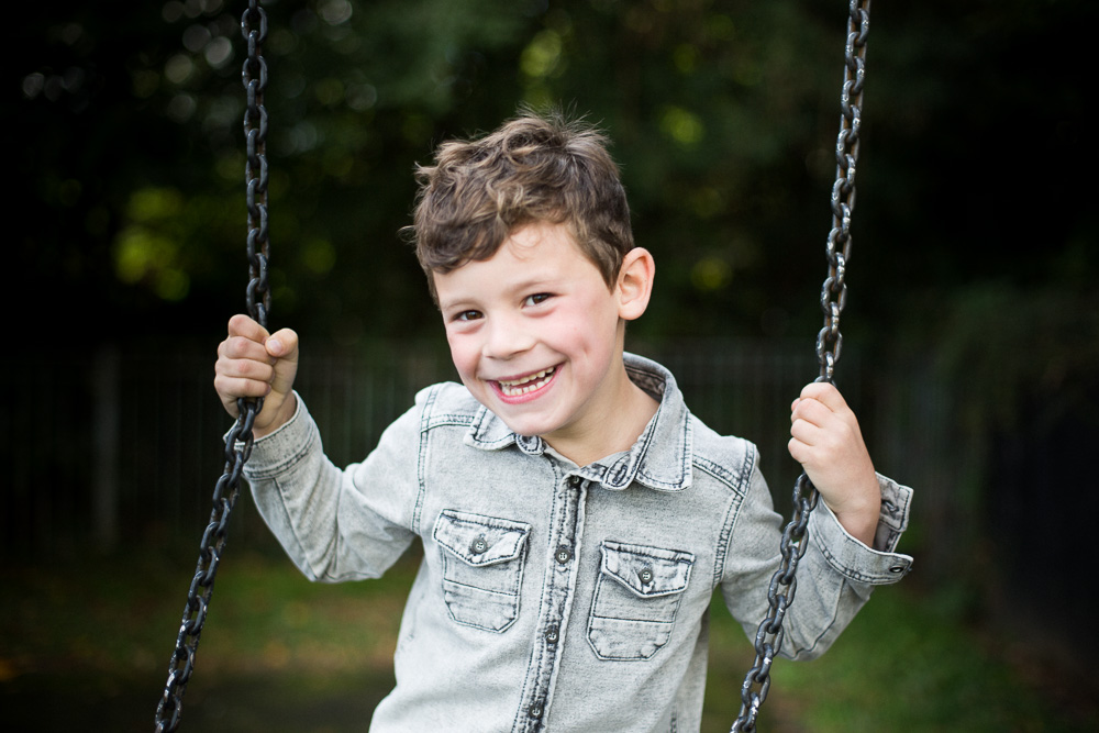 young boy smiling on a swing
