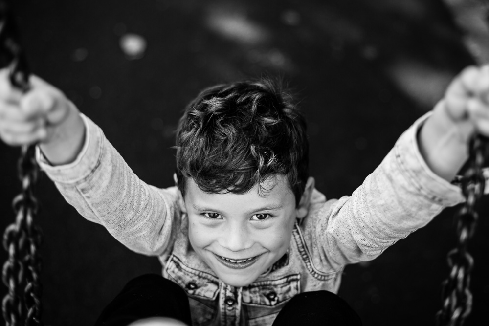 black and white photo of boy giggling on the swings