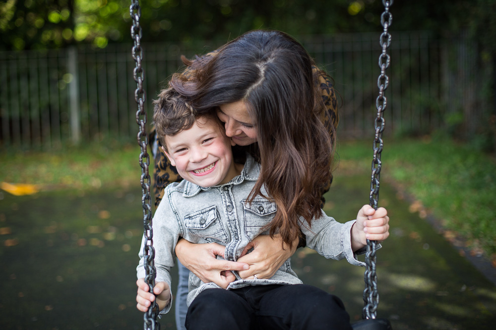mum giving a gentle kiss on son's head on the swings