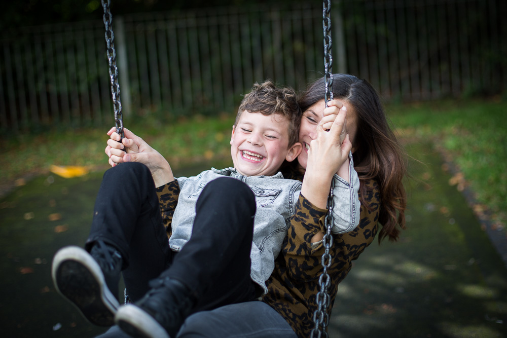 bride laughing on the swings with son