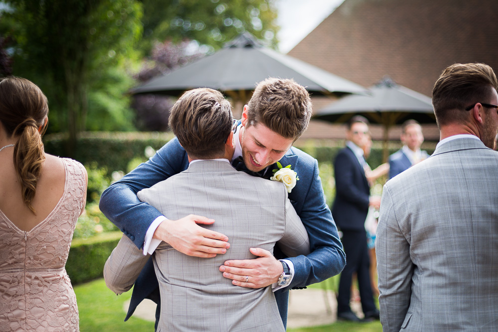 Groom hugging guest at The old Kent Barn