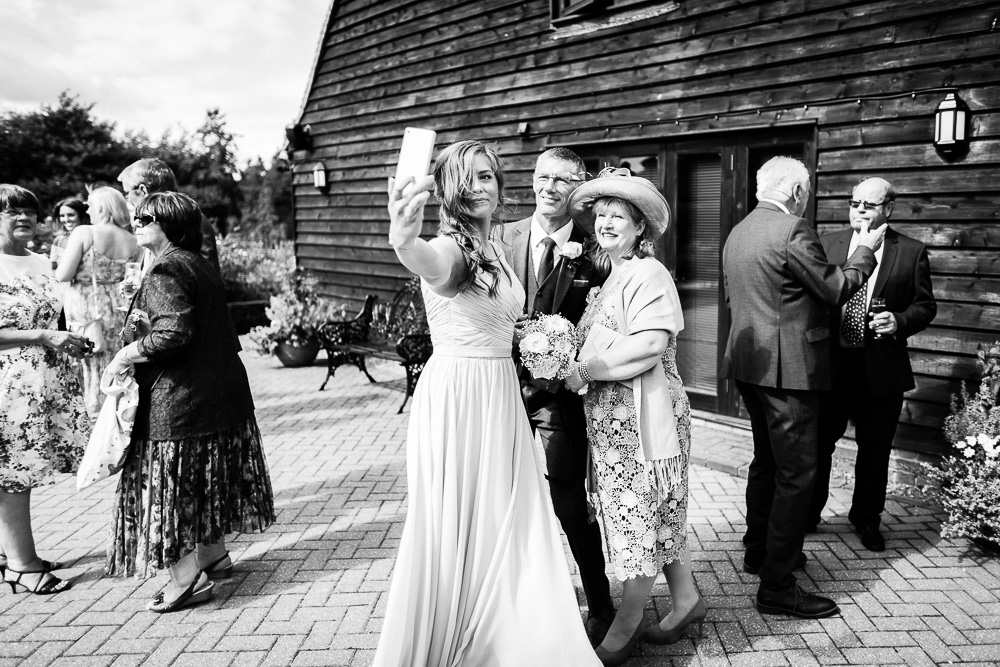 selfie in black and white of 3 wedding guests