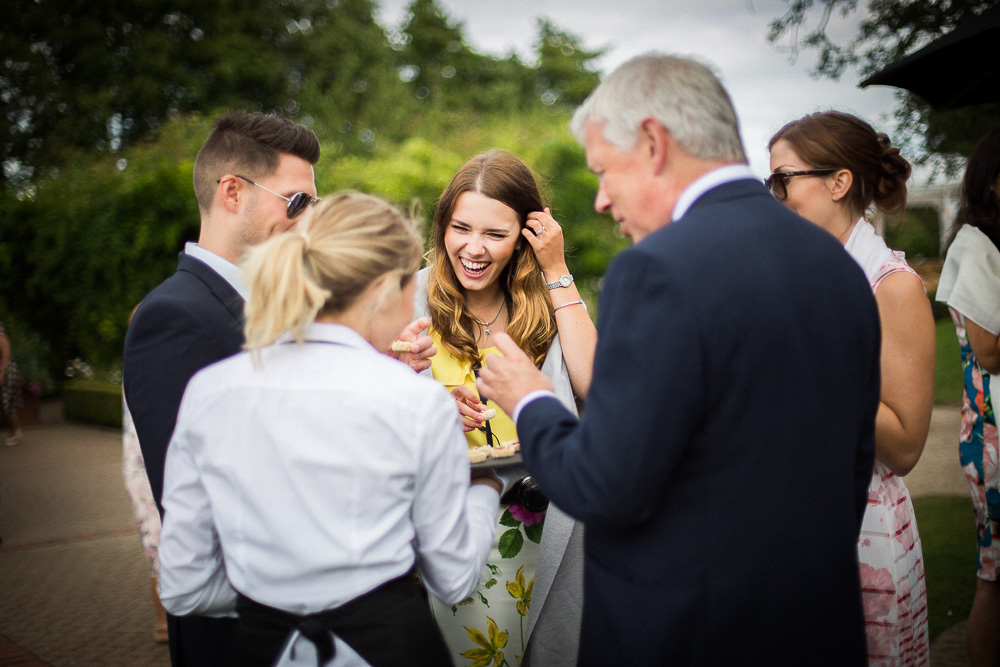 laughing guests eating canapés