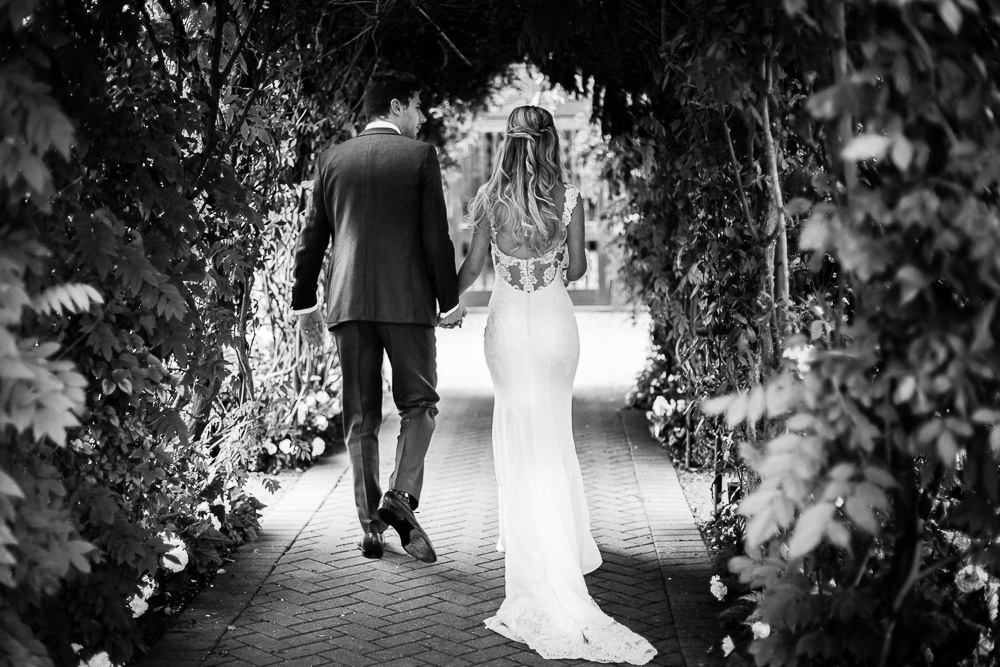 Bride and groom leaving after the ceremony back shot in black and white