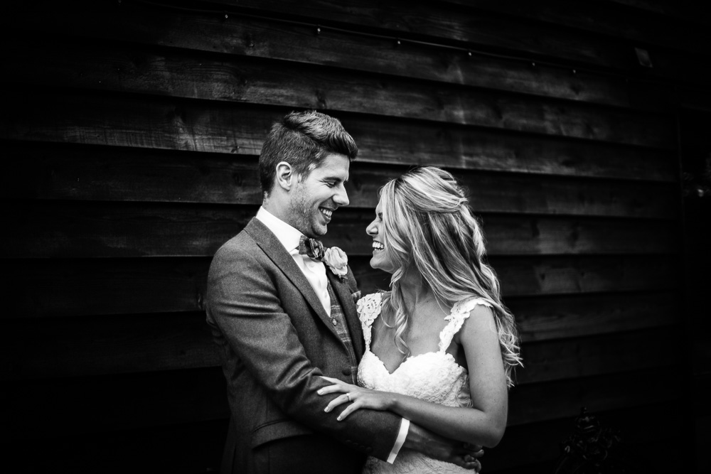 black and white portrait of bride and groom laughing
