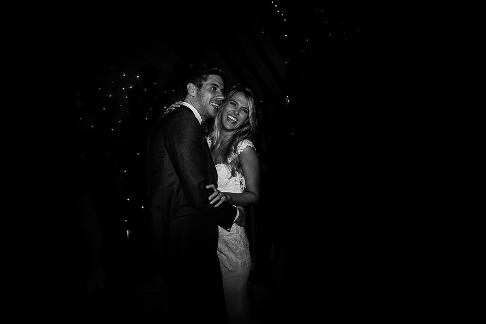 Bride and groom laughing during the first dance in black and white