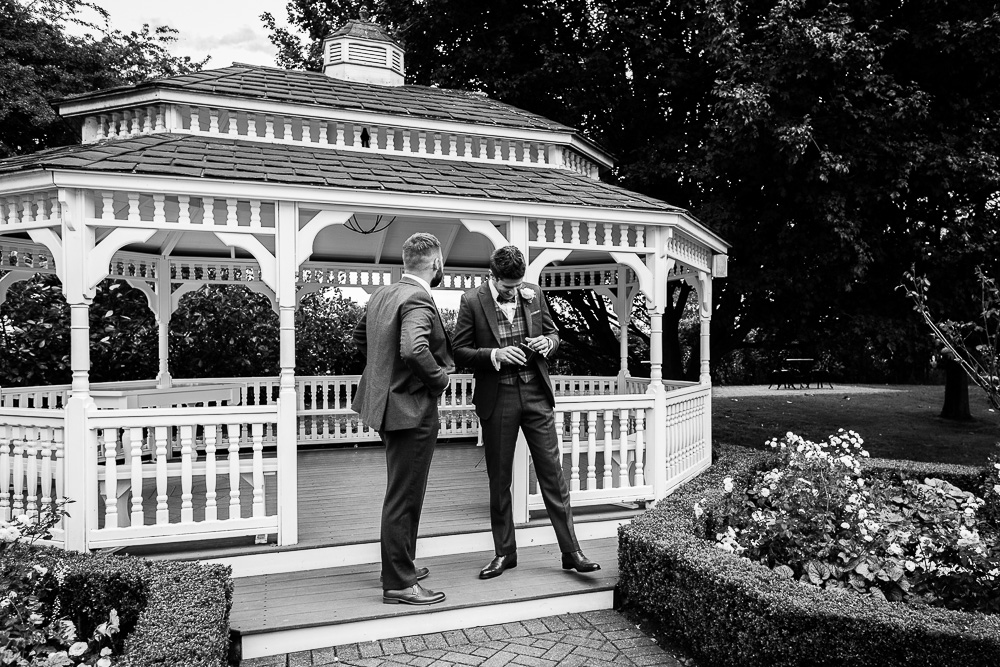 best man and groom having amoment black and white