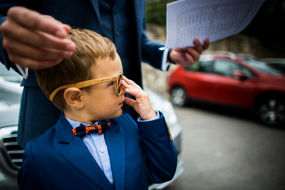 child wearing sunglasses looking at the groom