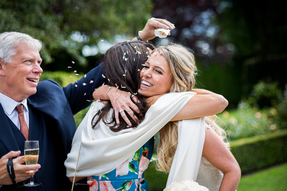 guest throwing confetti at bride