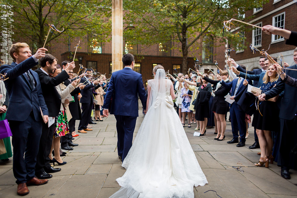 backshot of bride and groom outside temple church