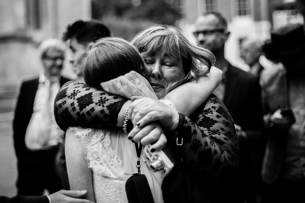 black and white shot of guest hugging the bride on the way to one whitehall place London
