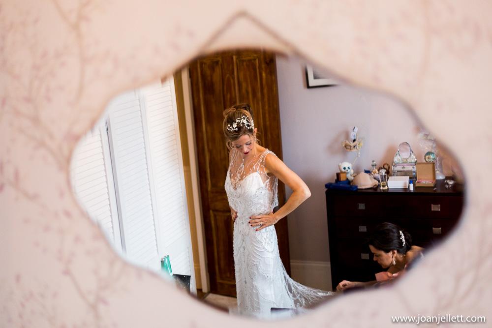 mirror shot of bride and bridesmaid ajusting the dress