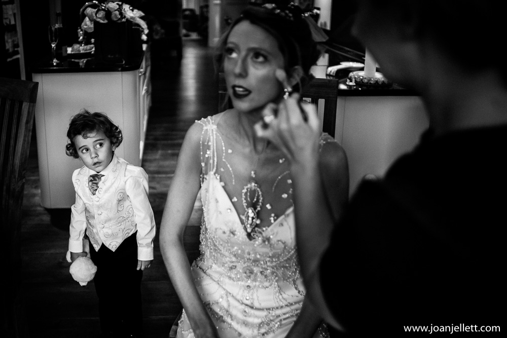black and white shot of little boy looking at bride having her makeup done