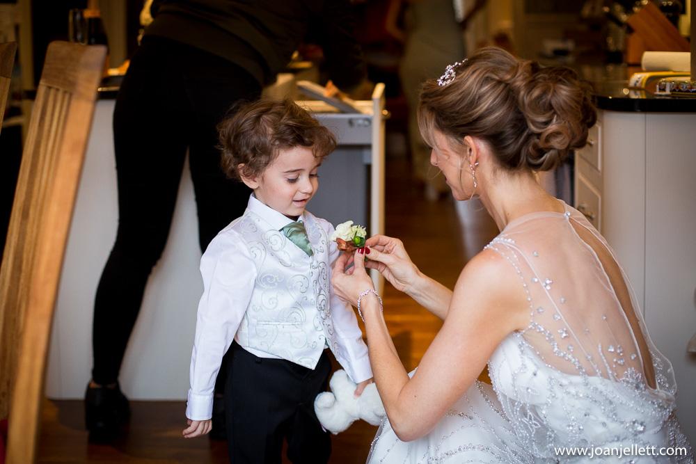 mum putting the flower on her little boy's waistcoat