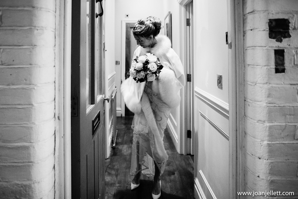 black and white shot of bride leaving the house
