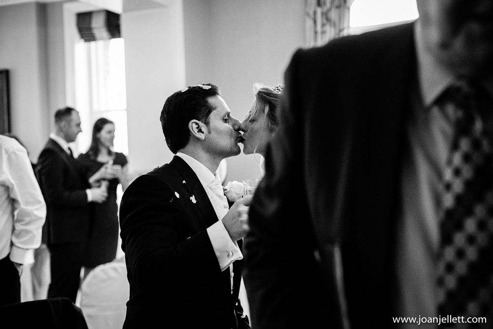 Groom kissing his bride in black and white