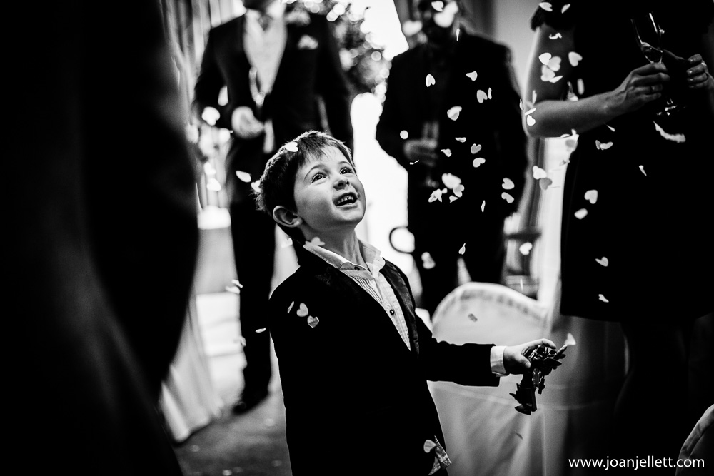 black and white shot of boy standing in confetti in petersham Hotel