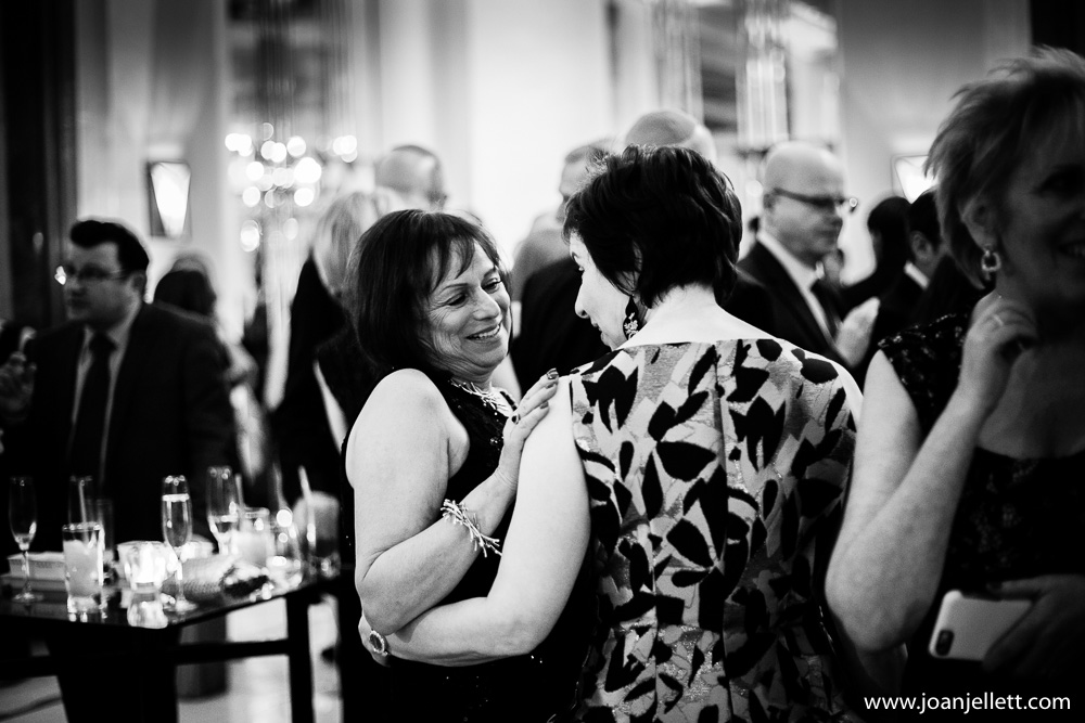 mum of the bride and guest talking during the reception in black and white