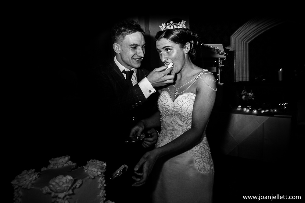 groom feeding bride wedding cake