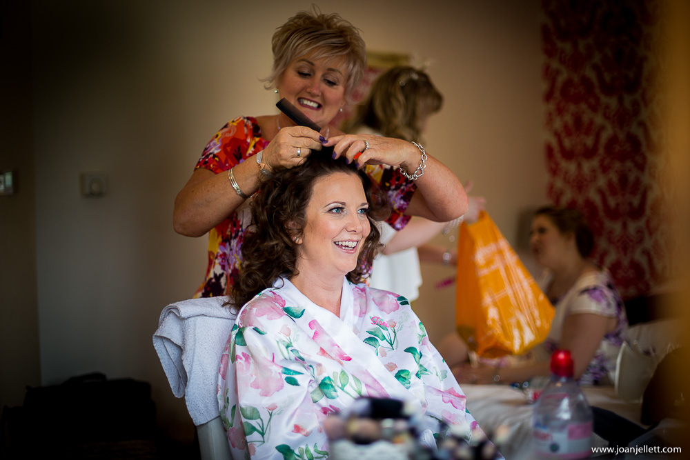 laughing bride having her hair done