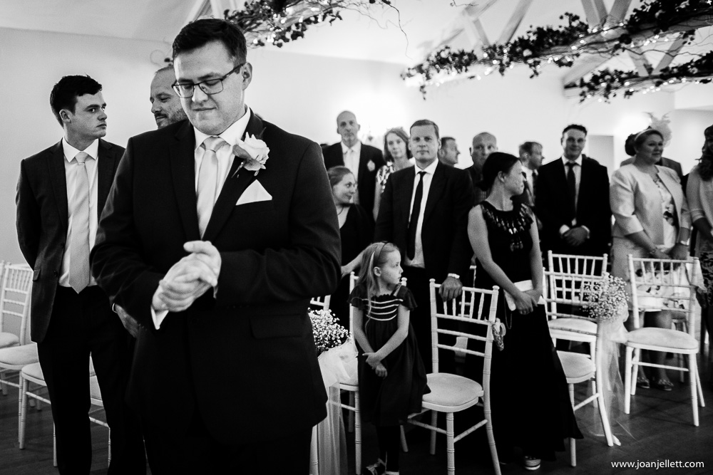 black and white shot of the nervous groom at the alter