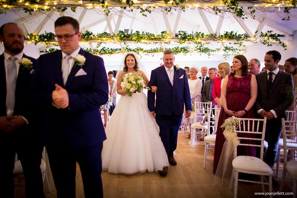 bride walks down the aisle smiling