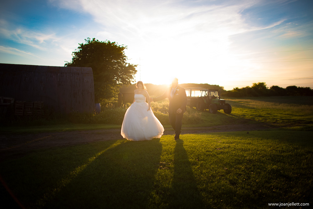bride and groom walking together at the sunset