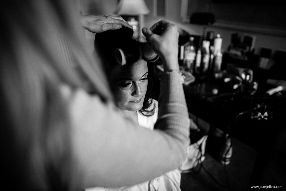 black and white shot of bride having her hair done