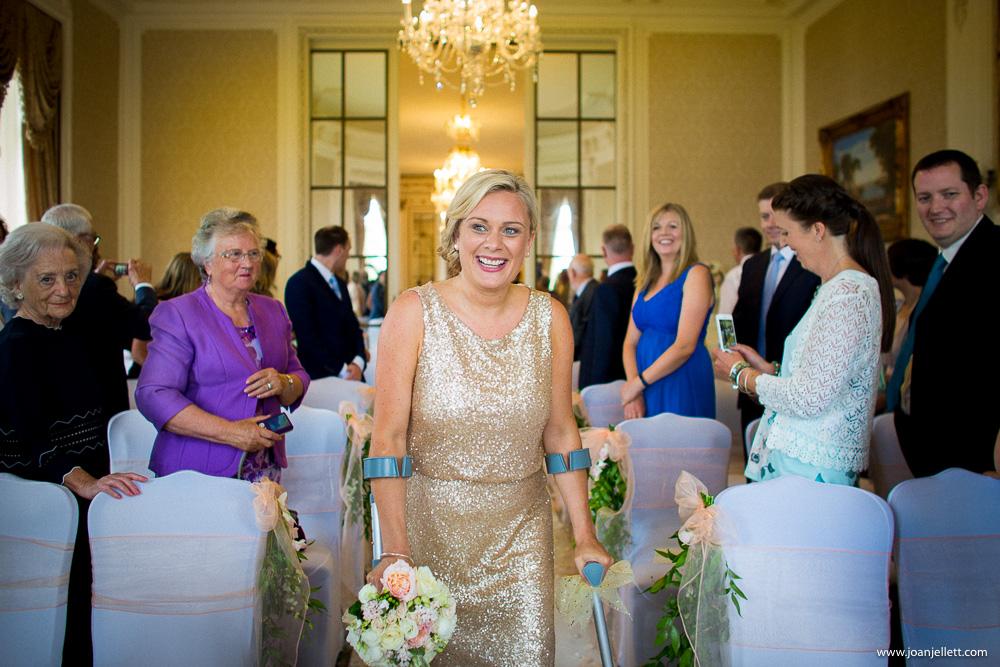 bridesmaid walking with crutches down the aisle