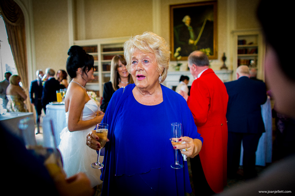mother of the bride holding 2 flutes of champagne