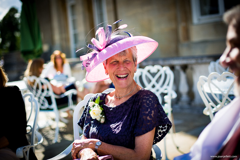 mother of the groom laughing in the sunshine in purple hat