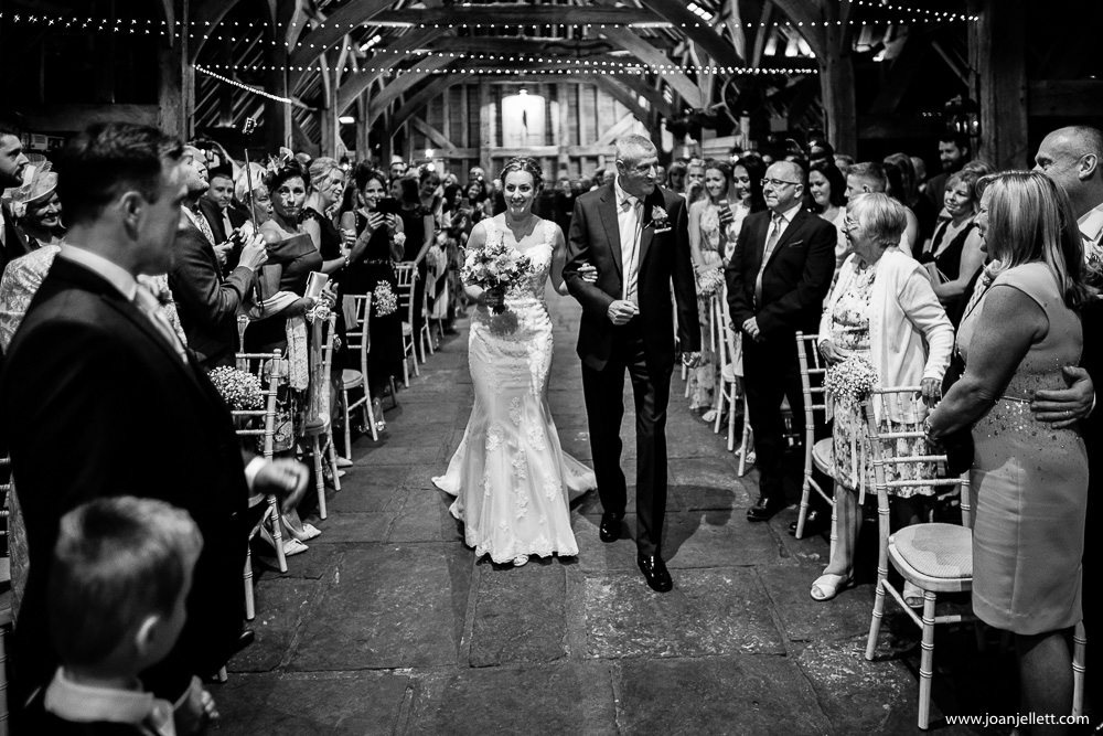 black and white shot of bride walking down the aisle