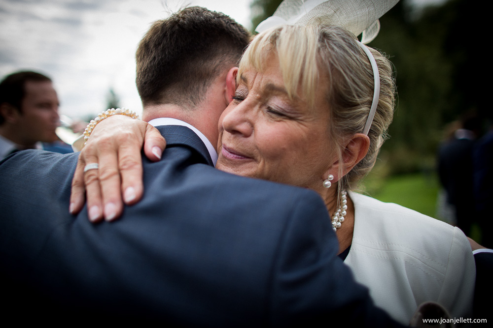 guest kissing the groom on the cheek