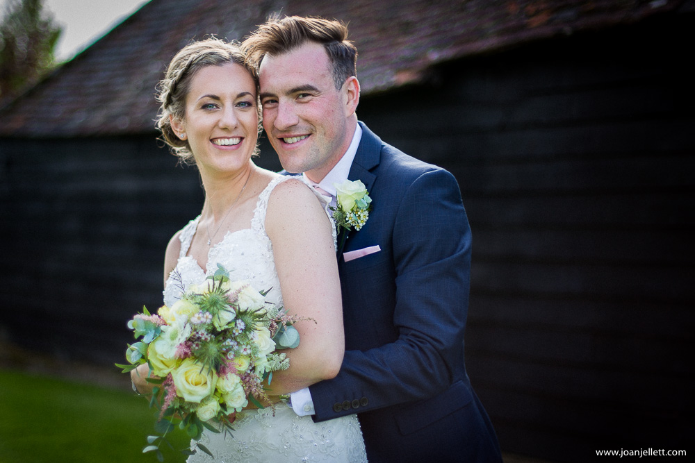 portrait of bride and groom in front of the barn