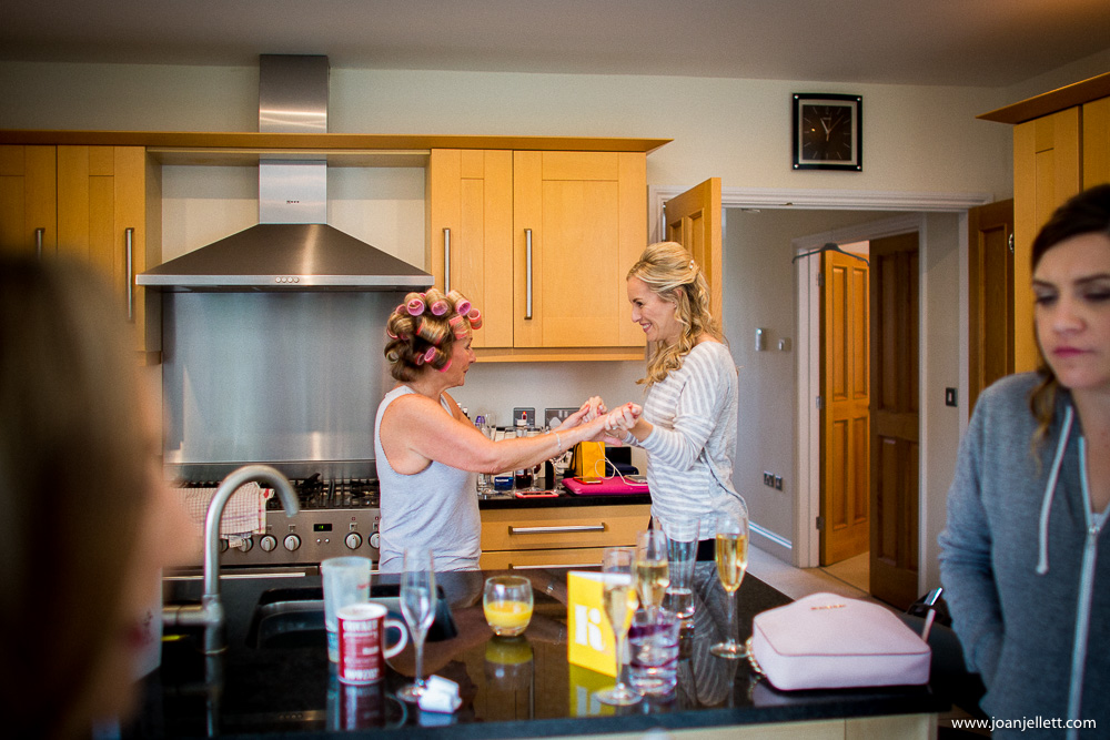 mother of the bride and bridesmaid dancing in the kitchen