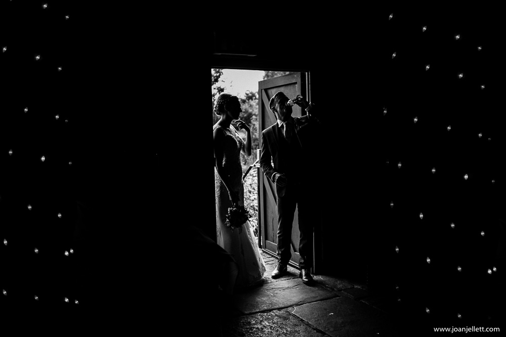 black and white shot of bride and groom drinking