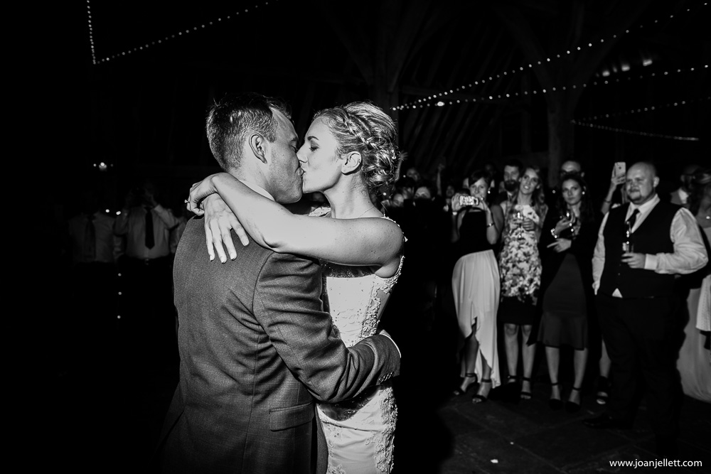 black and white shot of bride and groom kissing on the dance floor