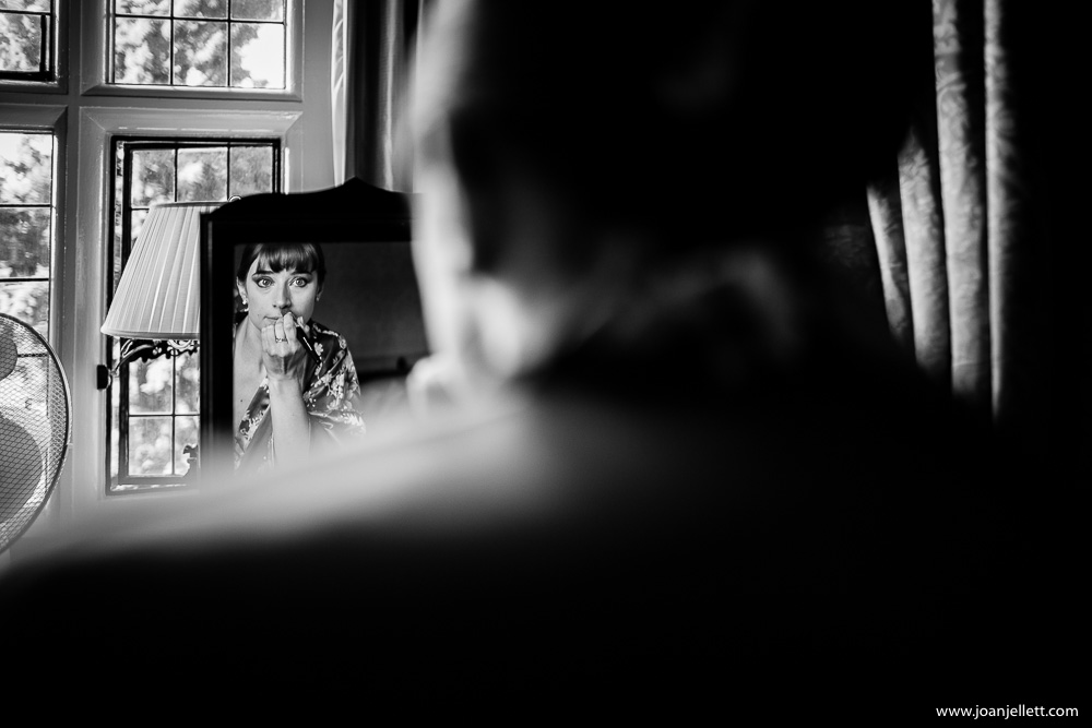 bridesmaid black and white in the mirror applying makeup